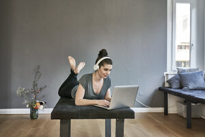 Young woman with headphones lying on lounge using laptop - FMKF04016