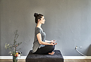 Young woman sitting on lounge doing yoga - FMKF04019
