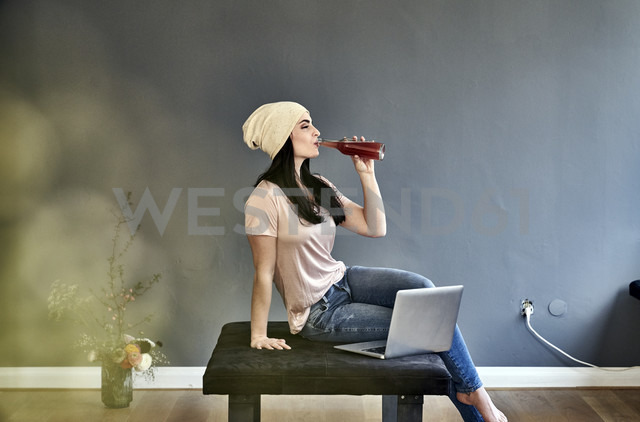 Young woman with laptop drinking from bottle - FMKF04022 - Jo Kirchherr/Westend61