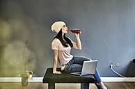 Young woman with laptop drinking from bottle - FMKF04022