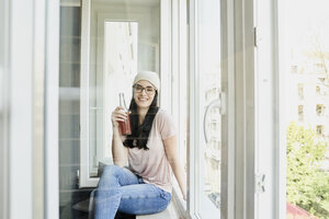 Portrait of smiling young woman holding bottle at the window - FMKF04028