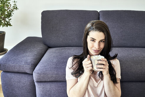 Smiling young woman with coffee mug at home - FMKF04037