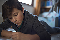 Boy lying on the floor at home doing homework - ZOCF00216