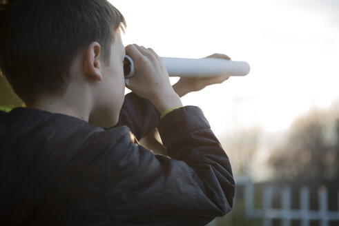 Boy watching something with home-made telescope - ZOCF00219
