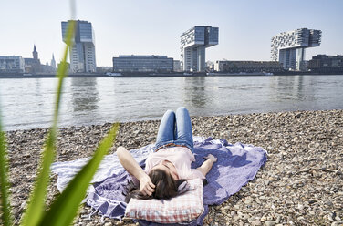 Germany, Cologne, young woman relaxing at River Rhine - FMKF04047