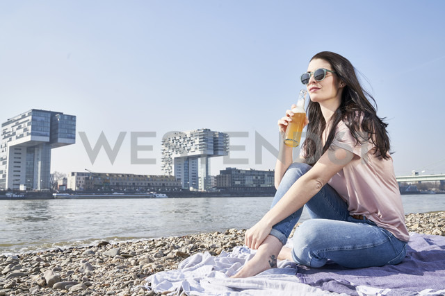Germany, Cologne, young woman relaxing and having a beer at River Rhine - FMKF04053 - Jo Kirchherr/Westend61