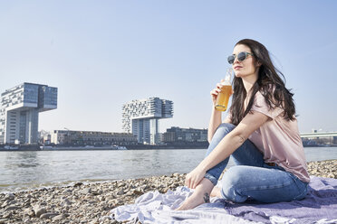 Germany, Cologne, young woman relaxing and having a beer at River Rhine - FMKF04053