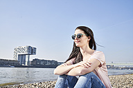 Germany, Cologne, young woman relaxing at River Rhine - FMKF04056