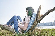 Young woman relaxing outdoors using tablet - FMKF04059
