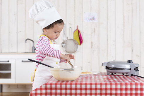 Little girl preparing waffles, wearing chef's hat - DRF01725