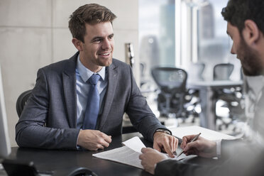 Businessman showing client where to sign document - ZEF13609