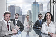 Portrait of confident businessmen and businesswomen sitting in conference room - ZEF13618