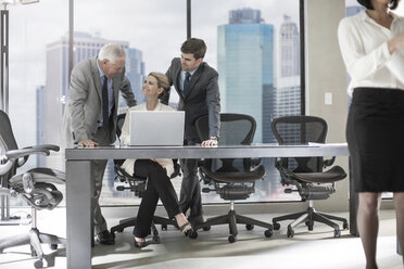 Group of businesspeople with laptop discussing in office - ZEF13645