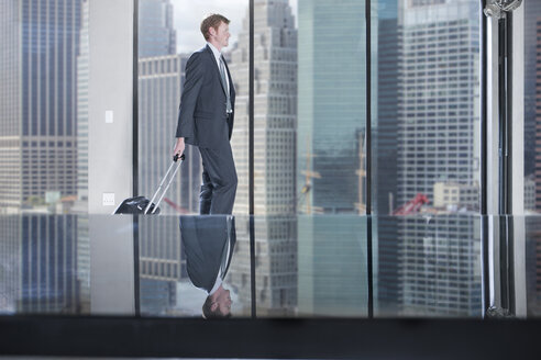 Businessman walking with rolling suitcase in city office - ZEF13654