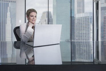 Smiling businesswoman sitting at desk in city office looking at laptop - ZEF13660