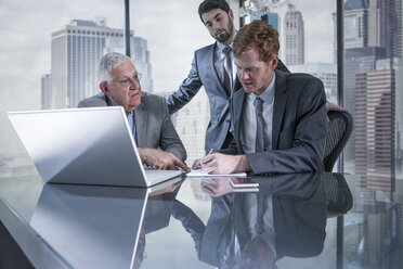 Three businessmen with laptop discussing in office - ZEF13663
