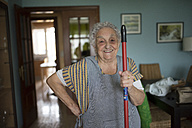 Portrait of smiling senior woman holding stick of cleaning mop - RAEF01864