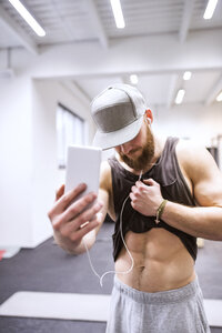 Young athete taking sixpack selfies in gym - HAPF01539