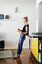 Ginger woman standing in kitchen eating breakfast - VABF01339