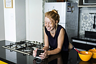 Young woman standing in kitchen, drinking coffee - VABF01345