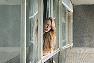 Ginger woman looking out of window - VABF01351