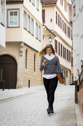 Germany, Tuebingen, smiling young student looking at cell phone while walking - MIDF00826