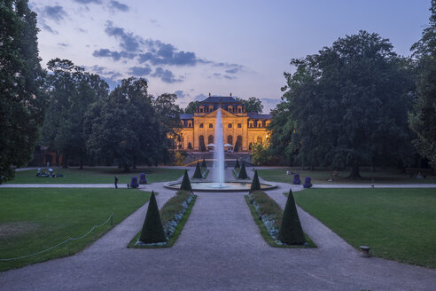 Germany, Fulda, view to palace garden and lighted orangery in the background at evening - PVC01092
