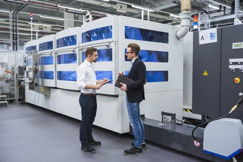 Two men talking in factory shop floor - DIGF02154