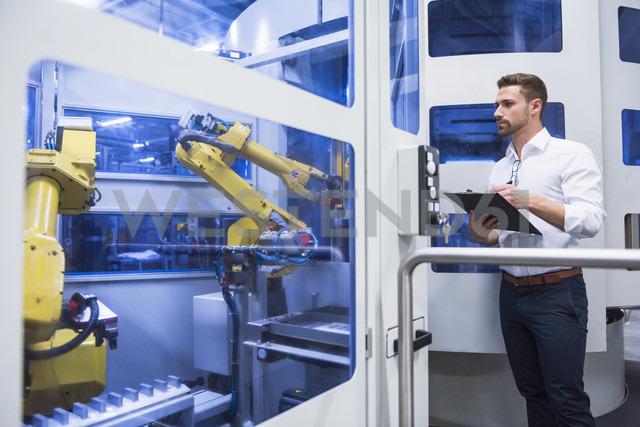 Man taking notes at robotics machine in factory shop floor - DIGF02166