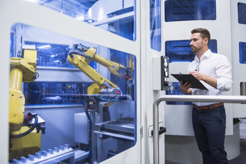 Man taking notes at robotics machine in factory shop floor - DIGF02166