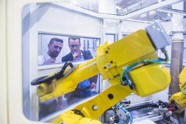 Two men in factory shop floor looking at robotics machine - DIGF02181