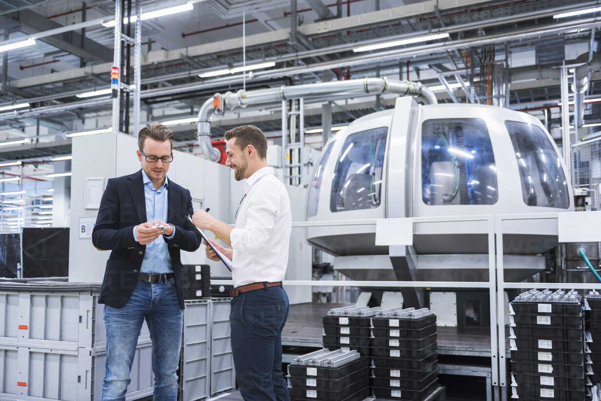 Two men in factory shop floor examining product - DIGF02184 - Daniel Ingold/Westend61