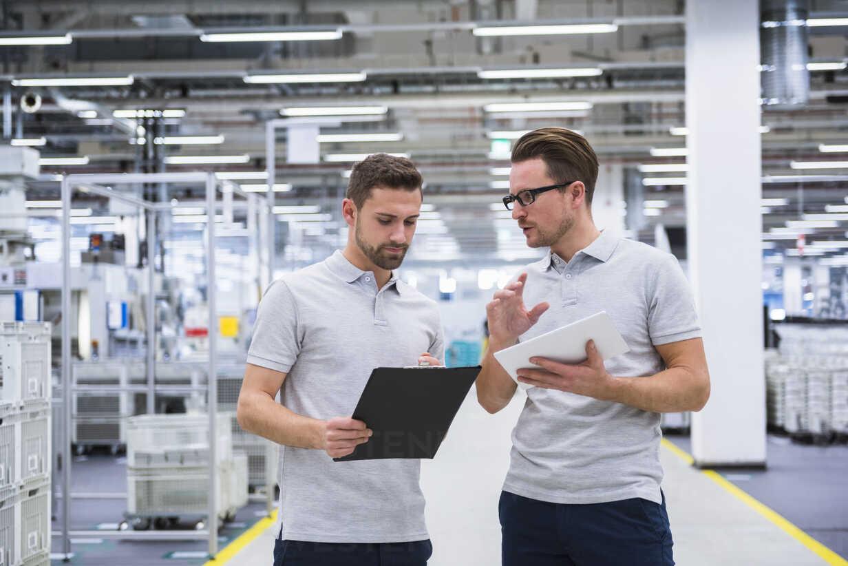 Two men talking in factory shop floor - DIGF02190 - Daniel Ingold/Westend61