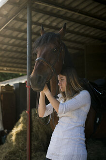Young woman with horse on farm - ZOCF00235