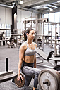 Young woman lifting weights in gym - HAPF01558