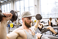 Young man exercising with dumbbells in gym - HAPF01576
