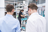 Two businessmen in factory shop floor with man in background working - DIGF02243