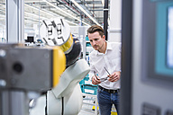 Man examining assembly robot in factory shop floor - DIGF02249