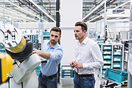 Two men with tablet examining assembly robot in factory shop floor - DIGF02252