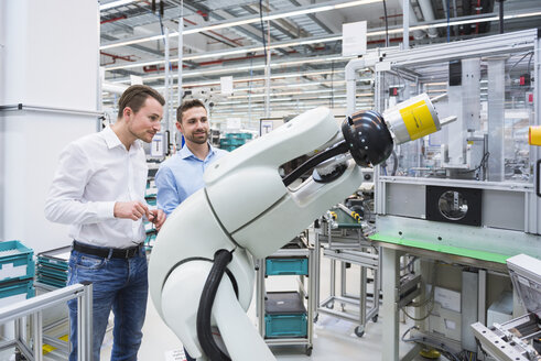 Two men looking at assembly robot in factory shop floor - DIGF02255