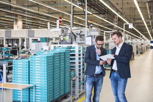Two men with tablet talking in factory shop floor - DIGF02258