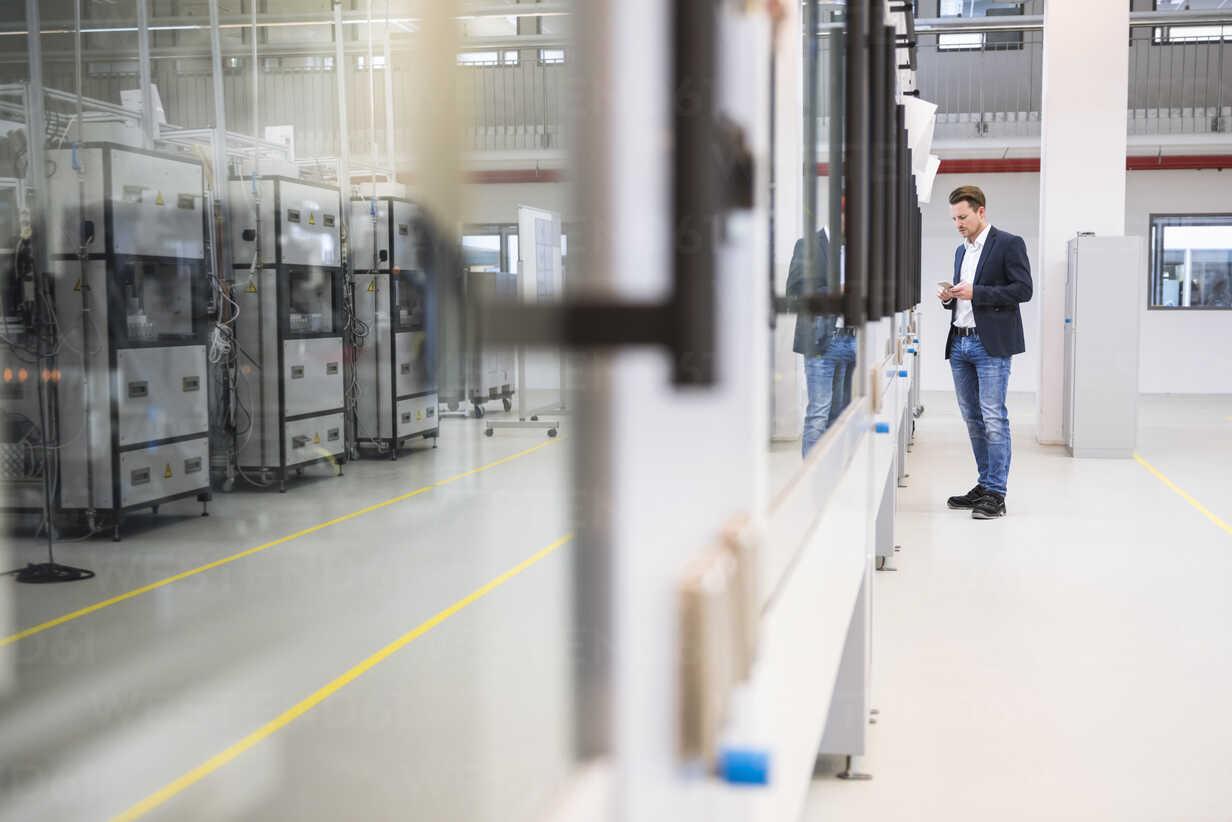 Man standing in factory shop floor - DIGF02264 - Daniel Ingold/Westend61