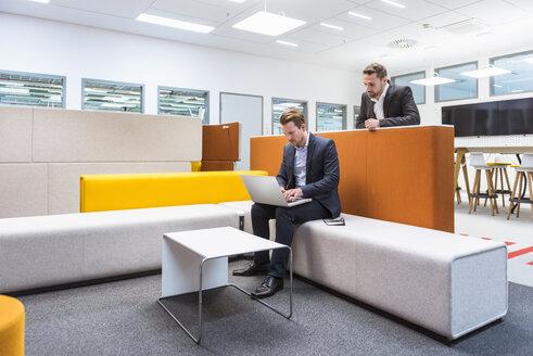 Businessman sitting in conversation pit, colleague watching him - DIGF02282