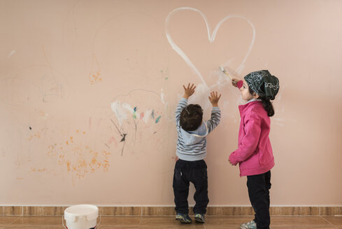 Little girl painting on wall in children's room while her brother watching - JASF01772