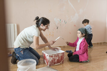 Mother and children painting wall in children's room - JASF01775