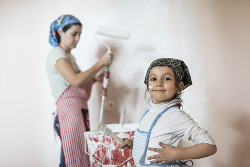 Portrait of little girl painting wall in children's room with her mother - JASF01778