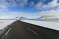 Empty road through Iceland with mountains in background - RAEF01868