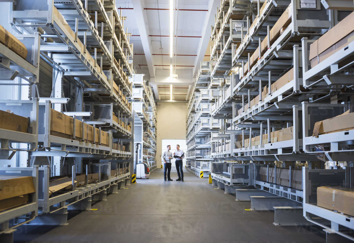 Two men standing in factory warehouse - DIGF02302 - Daniel Ingold/Westend61