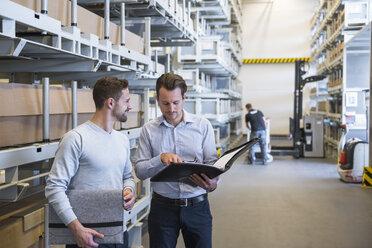 Two men talking in factory warehouse - DIGF02308
