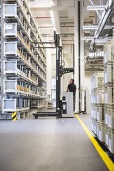 Worker operating forklift in factory warehouse - DIGF02317